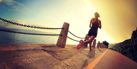 Fitness woman running on seaside trail in the morning Banco de Imagens