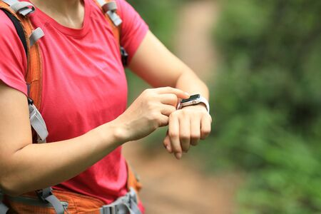Woman hiker checking on smartwatch on hiking travel