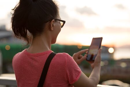 Woman use smartphone in sunset Hong Kong