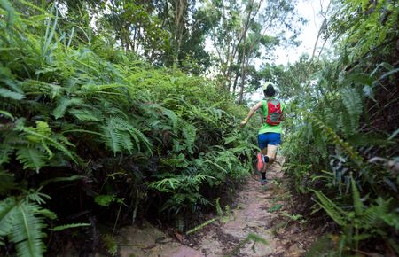 Woman ultra marathon trail runner running on tropical forest trail