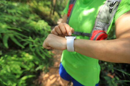 Asian woman trail runner set the sports watch before trail running on mountain 写真素材