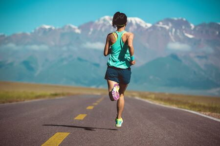 Rear view of fitness woman runner running on road Imagens