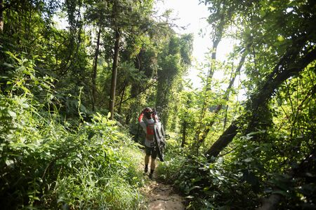 Woman cyclist carry a mountain walking on tropical forest