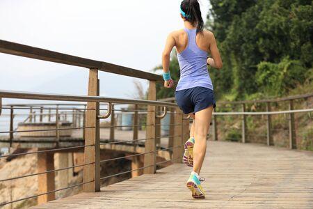 Sporty female runner running on seaside boardwalk