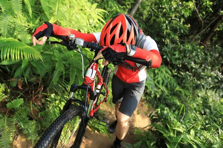 Tired woman cyclist have a rest while cross country biking in tropical forest