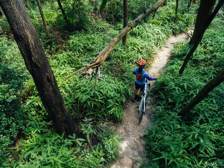 Cross country biking woman cyclist with mountain on tropical forest trail