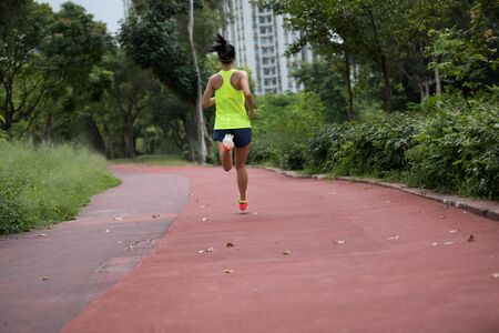 Fitness sporty woman jogger running at outdoors jogging track in park Banco de Imagens