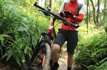 Riding on summer hill, holding mobile phone, using online application for searching GPS coordinates while riding bike in forest on sunny day