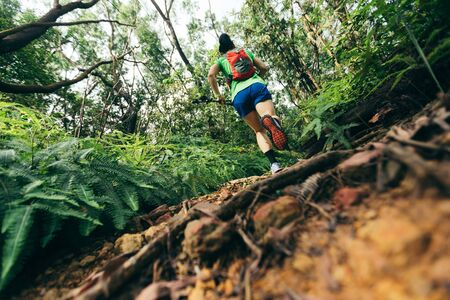 Woman ultra marathon runner running on tropical forest trail