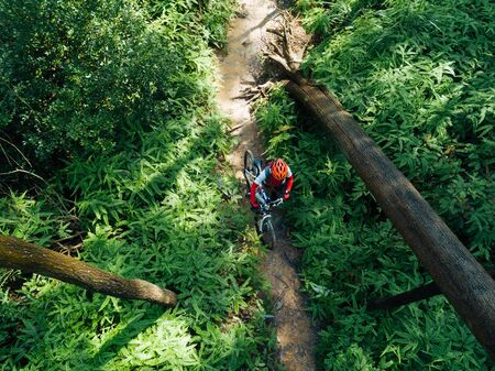 Woman cyclist with a mountain walking on tropical forest