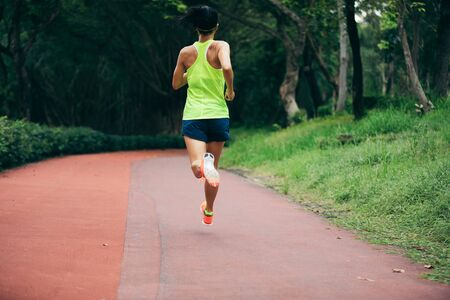 Fitness sporty woman jogger running at outdoors jogging track in park Imagens