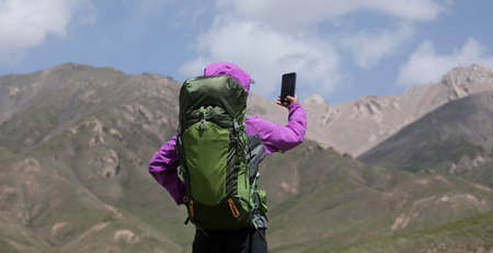 Successful woman hiker taking photo with smartphone on high altitude mountain top Banque d'images