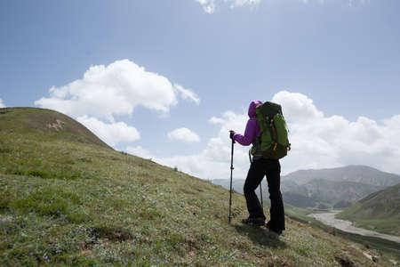Successful woman hiker climbing to high altitude mountain top