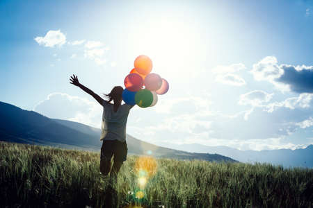Cheering young woman running on sunset grassland with colored balloons