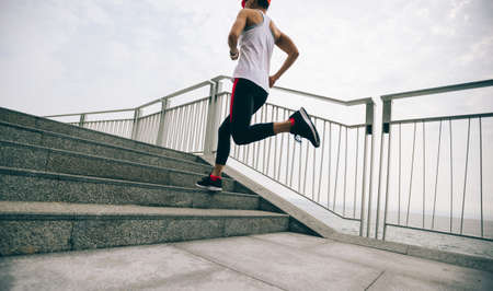 Healthy lifestyle fitness sports woman runner running up stairs on seaside trail