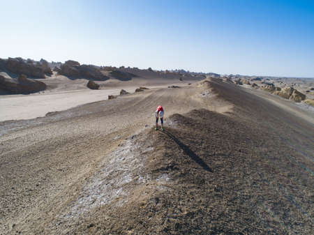 Tried woman trail runner taking a breack on sand desert dunes