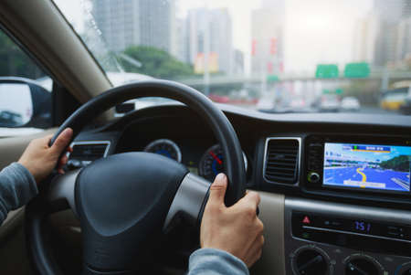 People hands holding steering wheel while driving car on city road Banco de Imagens