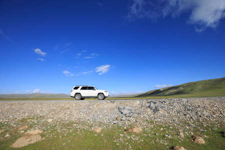 Driving offroad car on trail in high altitude grassland