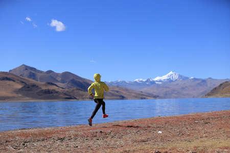Woman trail runner cross country running in winter lakeside Banco de Imagens