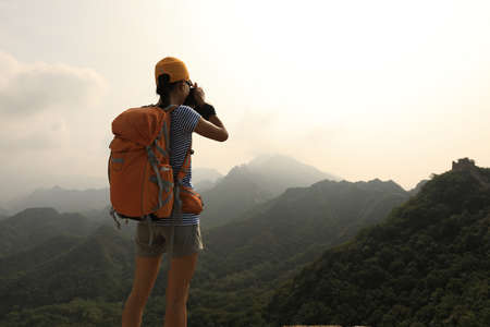 Woman hiker taking photo on the top of mountain