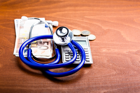 hospital expenses: Stethoscope on a calculator and money