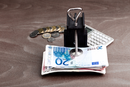 euro screw: Budget: money in a clamp with a calculator in the background