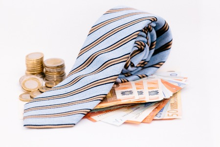 bank notes: A necktie on pile of bank notes with coins on the side Stock Photo