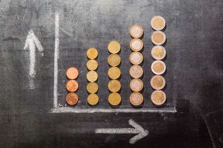proceedings: A graph on a black board made up with coins showing growth