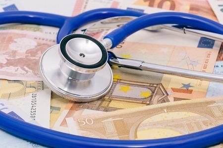 Stetoscopio su un mucchio di soldi, analizzando i costi sanitari Archivio Fotografico