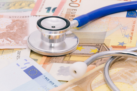 cost: Stethoscope on a pile of money, analyzing health care costs