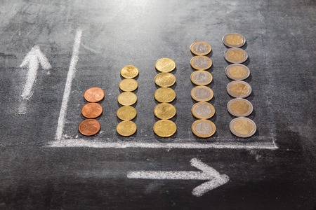 A graph on a black board made up with coins showing growth