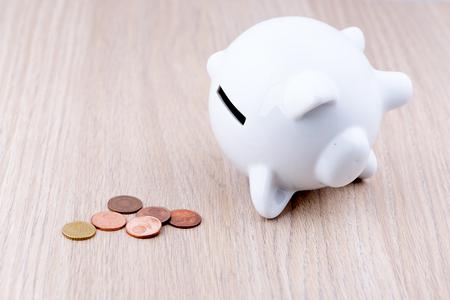 banco dinero: hucha blanco sobre un escritorio de madera: es en su lado con unos pocos c�ntimos, un concepto de un presupuesto ajustado