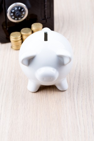 depositing: White piggy bank with black metal coin bank in background: a concept for either withdrawing or depositing money Stock Photo