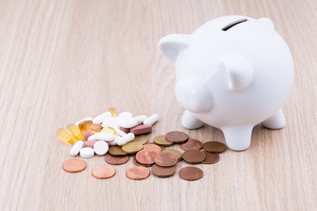 health care funding: White piggy bank on a wooden desk with coins and medicine