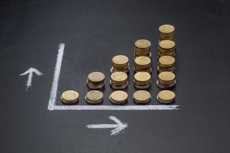 money concept: A graph on a clean black board made up with coins showing growth
