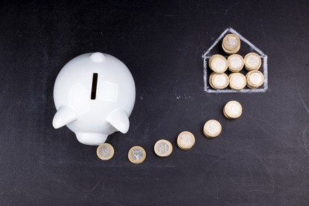 homeownership: White piggy bank on blackboard: saving for a house, coins and a drawing of a house Stock Photo