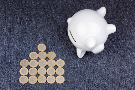 homeownership: White piggy bank on dark background: saving for a house, coins in the shape of a house Stock Photo