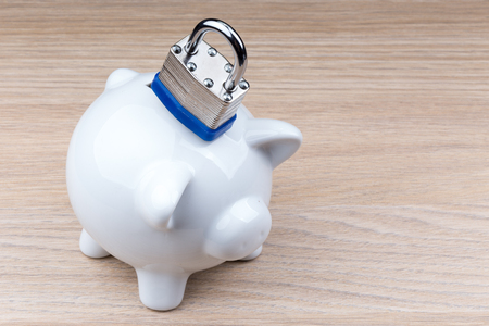 lockup: Piggy bank with padlock on wooden table