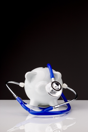 surgery expenses: Piggy bank with a stethoscope on a black background - medical costs concept