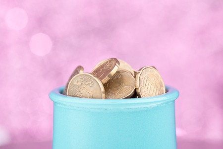 withdraw: Blue pot full of coins on pink blurry background