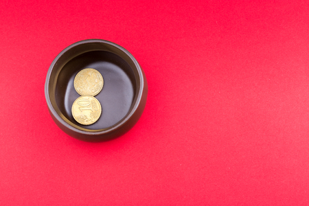 indebted: A pot on its side with a few coins, a concept of a tight budget