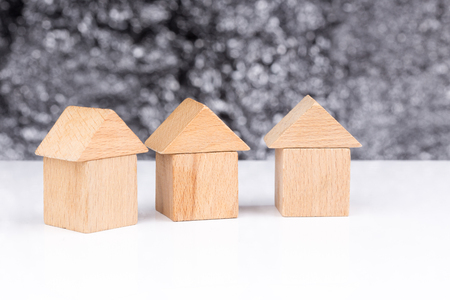 homeownership: Three houses made of wooden blocks with a blurry background