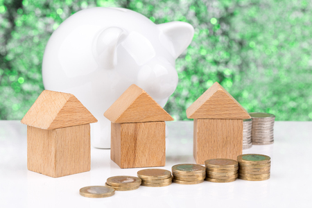 homeownership: Wooden block houses and coin stacks in a row with a green background Stock Photo
