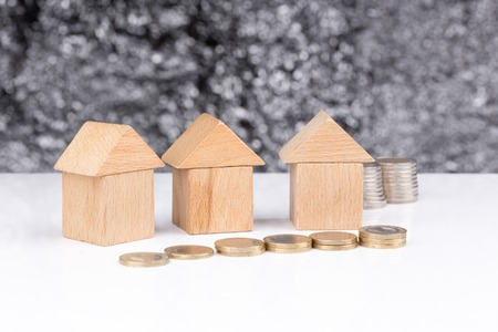 homeownership: Three houses made of wooden blocks with a blurry background and coins