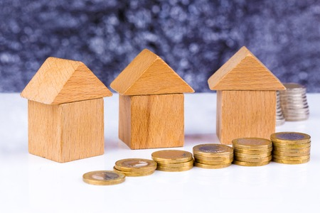 homeownership: Wooden block houses and coin stacks in a row Stock Photo