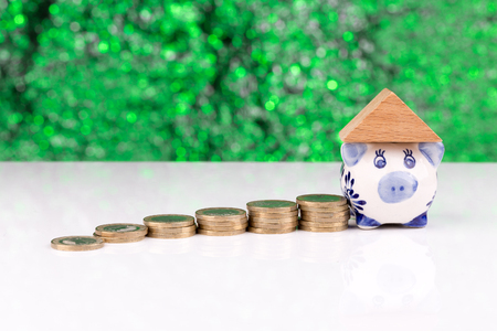 homeownership: Wooden block houses and coin stacks in a row with a green background and a piggy bank