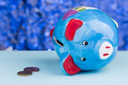 Blue piggy bank on a blue background: its on its side with a few pennys, a concept of a tight budget