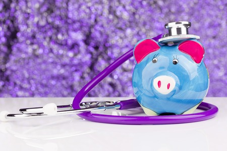 hospital fees: Close up of a stethoscope with a piggy bank Stock Photo