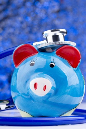 hospital expenses: Close up of a stethoscope with a piggy bank Stock Photo