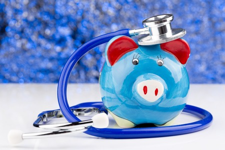 Close up of a stethoscope with a piggy bank Stock Photo